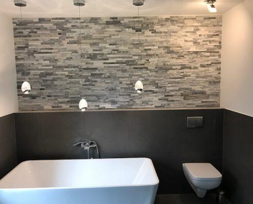 Badewanne und WC vor Steinwand